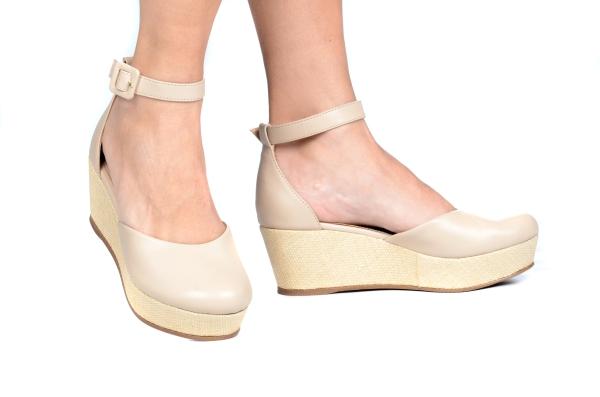 Sapato estilo espadrille em couro sintético com bico fechado e calcanhar fechado. Tira de fivela no tornozelo. Salto revestido em palha de 5,5 cm com plataforma de 3 cm, o que deixa a curvatura do pé com apenas 2,5 cm, proporcionando mais conforto e estab